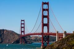 Golden gate bridge med segelbåten i vatten Fotografering för Bildbyråer