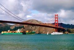 Golden gate bridge mit dem Führen des Containerschiffs und der Fähre Stockfoto