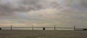 Golden gate bridge op een bewolkte hemel wordt gesilhouetteerd die stock afbeeldingen