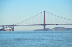 Golden Gate Bridge over the bay in San Francisco, California. The Golden Gate Bridge, a California landmark, next to mountains and over the San Francisco Bay on Stock Photo
