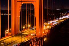 Golden gate bridge på natten med bil- och skeppslingor arkivbilder