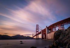 Golden gate bridge på solnedgången med dramatiska himlar Fotografering för Bildbyråer