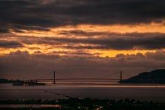 Golden gate bridge på solnedgången med tjocka lynniga moln royaltyfri fotografi