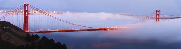 Golden Gate Bridge panoramic. Fog rolls the Golden Gate Bridge at dusk. The city of San Francisco is in the background. Panoramic composition stock images