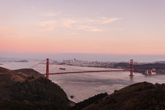 Golden Gate Bridge in pink glow of twilight mountains, skyline Stock Photos
