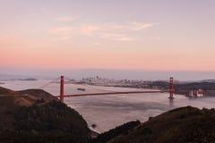 Golden Gate Bridge in pink glow of twilight mountains, skyline Stock Photos