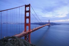 Golden Gate Bridge and ruins of old fortification. A traffic flows along the glowing Golden Gate Bridge behind ruins of old fortification Royalty Free Stock Photos