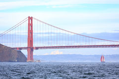 Golden Gate Bridge and sailboat with red sails approaching  in light fog Stock Images
