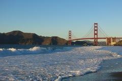 Golden Gate Bridge San Francisco from Baker Beach. Surf crashes on Baker Beach as the Golden Gate Bridge in San Francisco looms in the distance Royalty Free Stock Photo