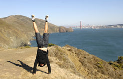 Golden gate bridge, San Francisco Bay, California. Imge of a young man doing handstand in front of the Golden Gate bridge in San Francisco, California. Image Stock Image