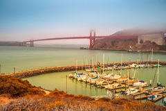 Golden Gate Bridge Sausalito. Aerial view of Golden Gate Bridge with typical fog and Presidio Yacht Club in Horseshoe Bay, Sausalito, California, United States Royalty Free Stock Photo