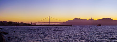 The Golden Gate Bridge silhouetted at sunset. A freighter drifts through the San Francisco Bay en route through the Golden Gate Royalty Free Stock Photography