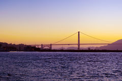 The Golden Gate Bridge silhouetted at sunset. The Golden Gate Bridge and the indigo waters of the San Francisco bay at sunset Royalty Free Stock Photo