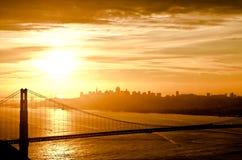 Golden Gate Bridge during sunrise. Morning sky over Golden Gate Bridge during sunrise with city skyline Royalty Free Stock Images