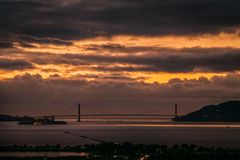 Golden Gate Bridge at sunset with thick moody clouds royalty free stock photography