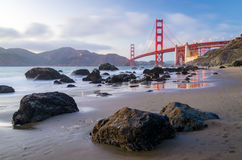 Golden Gate Bridge during the sunset, view from the beach, water reflections Royalty Free Stock Photo