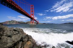 Golden Gate Bridge and surf on the rocks. Surf splashes over rocks under Golden Gate Bridge as seen from the Fort Point beach Royalty Free Stock Photography