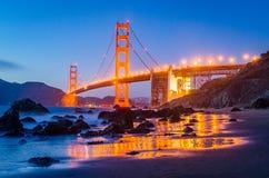Golden gate bridge under solnedgången, sikt från stranden, vattenreflexioner Royaltyfri Bild