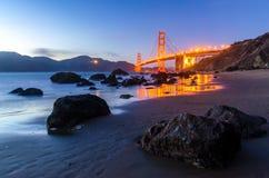 Golden gate bridge under solnedgången, sikt från stranden, vattenreflexioner Royaltyfri Foto