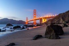 Golden gate bridge under solnedgången, sikt från stranden, vattenreflexioner Fotografering för Bildbyråer