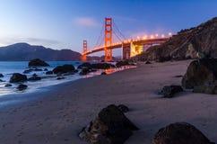 Golden gate bridge under solnedgången, sikt från stranden, vattenreflexioner Arkivbilder
