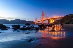 Golden gate bridge under solnedgången, sikt från stranden, vattenreflexioner Arkivbild