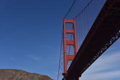 Golden Gate Bridge Vertical from Underneath. This view of the Golden Gate Bridge is from under it just as we pass the massive tower. The sky is crystal clear royalty free stock photo