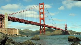 Golden Gate Bridge with waves. This video is about San Francisco`s Golden Gate Bridge from a low angle showing a rocky shore and waves cascading over the rocks stock video footage