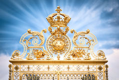 Golden gate Chateau Versailles. Golden ornate gate of Chateau de Versailles with blue sky, with clouds background. Rays of light from gate. Paris, France royalty free stock image