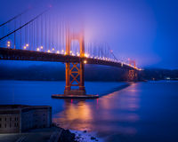 Golden Gate in Fog. Long exposure of the Golden Gate Bridge partially hidden in fog. Lights reflected on the smooth water of San Francisco Bay. Fort Point is in stock photo