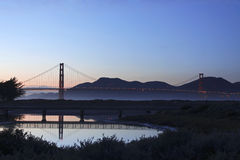 Golden Gate Night. A night shot of the Golden Gate Bridge in San Francisco, CA, with a clear sky and the bridge reflecting in water in the foreground Royalty Free Stock Photos