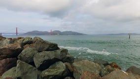 Golden Gate over groene wateren van de Baai met massieve rotsen op de voorgrond stock videobeelden
