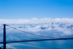 Golden Gate and San Francisco. Golden Gate Bridge and the city just peaking through the famous SF fog Stock Images