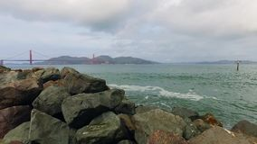 Golden Gate sobre las aguas verdes de la bahía con las rocas masivas en el primero plano almacen de metraje de vídeo