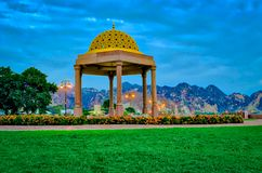 Resting place for people in Muttrah Corniche. Golden Gazebo dome surrounded by green lawns, as a resting place for people in the Muttrah Corniche Park, Muscat royalty free stock photo