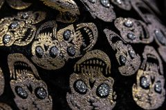 Golden Gem Skulls Rhinestones Fabric Texture Pattern Closeup Hal. Loween Decoration Stock Photo