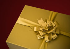 Golden gift. Gold gift with bow on red background Royalty Free Stock Photo