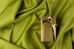 Golden gift box. A detail of a small golden gift box on green satin background Royalty Free Stock Images