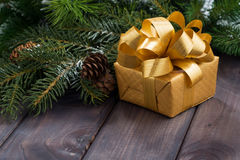 Golden gift box on the background of fir branches Stock Image