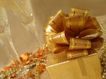 Golden gift box on a beautiful background with champagne glasses royalty free stock photography