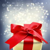 Golden gift box with big red ribbon Stock Photos