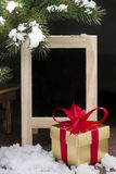 Golden gift box and blackboard on wooden floor with snow Stock Images