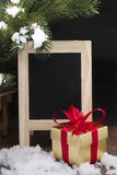 Golden gift box and blackboard on wooden floor with snow Stock Image