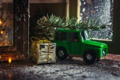 Golden gift box and christmas decoration object with Green toy car carrying a christmas tree on wood table with white background. royalty free stock image