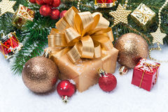 Golden gift box and Christmas decorations in the snow Stock Image