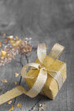 Golden gift box for christmas on a grey shabby chic background wi Stock Photos
