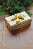 Golden gift box with christmas presents and branch of xmas tree with golden balls. On wooden background Royalty Free Stock Photos