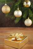 Golden gift box with christmas presents and brunch of xmas tree with golden balls Royalty Free Stock Images
