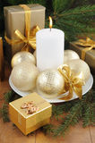 Golden gift box with christmas presents and brunch of xmas tree with golden balls. On wooden background Stock Photography