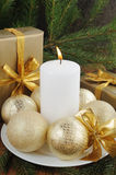 Golden gift box with christmas presents and brunch of xmas tree with golden balls. On wooden background Royalty Free Stock Photo